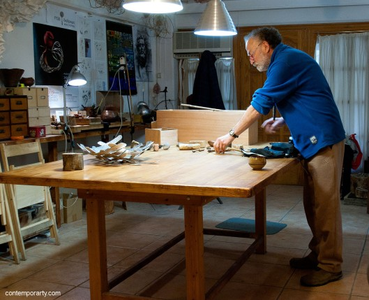 Akis Goumas is placing replicas of ancient tools on the table. He has created them and uses them to re-create ancient techniques in jewellery-making. The big wooden box is the actual size of an ancient workshop. Craftsmen carried their tools in these boxes on their journeys around Greece. Photograph by Eleni Roumpou